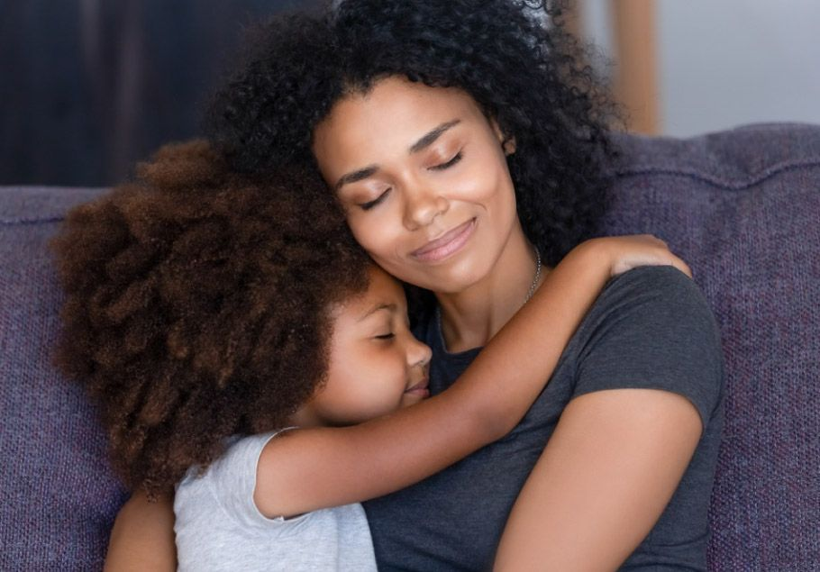 African American young mother holding young daughter